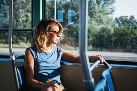 Young woman riding a public bus on a sunny day