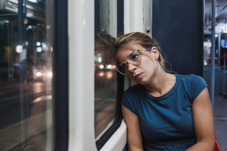 Young woman riding a public bus at night