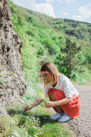 careless: Young woman picking flowers by the road