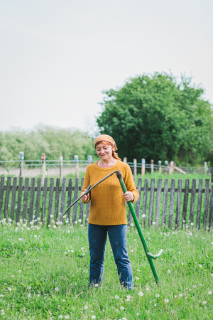 Mature female worker sharpening the scythe in the field