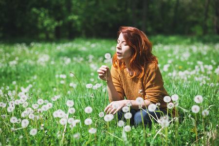Young woman blowing dandelion in the field Archivio Fotografico