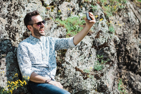 Young stylish man taking a selfie in nature
