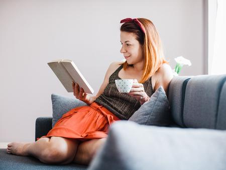 젊은여자가 커피를 마시는 독서 책을 마시는 거실에 앉아