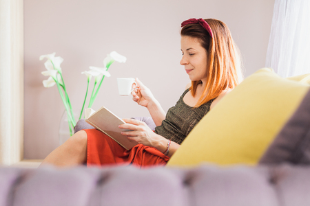 Young woman sitting in the living room drinking coffee reading book Archivio Fotografico