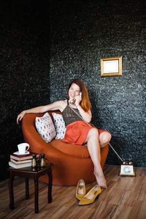 안락의 자에 앉아 전화로 얘기하는 젊은 여자