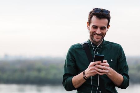 그의 스마트 폰에서 음악을 듣고 젊은 남자 스톡 콘텐츠