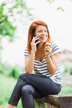 Young smiling woman talking on the phone in the park