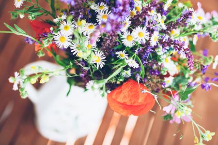야생 허브와 꽃병에 흰색 꽃병의 무리