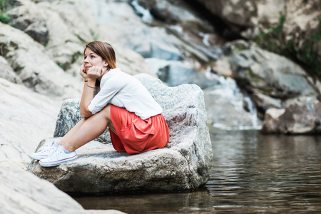 Young woman daydreaming by the river