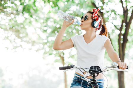 Young woman drinking water sitting on the bicycle Archivio Fotografico