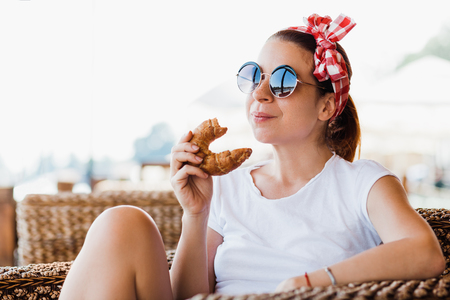 Young woman eating croissant in a cafe