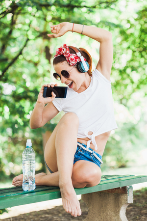 Young woman listening to the music on her smartphone