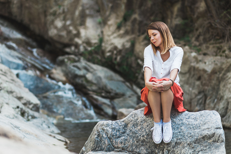 Young woman sitting on the rock by the river thinking
