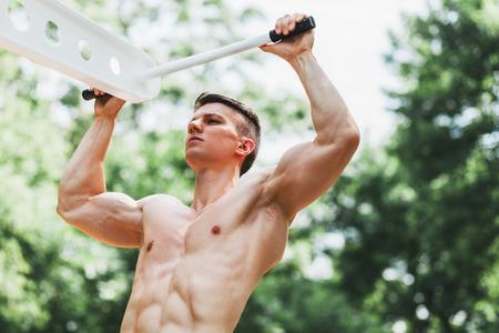 Joven musculoso haciendo pull ups en un gimnasio al aire libre