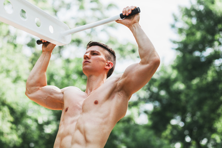 Young muscular man doing pull ups in an outdoors gym