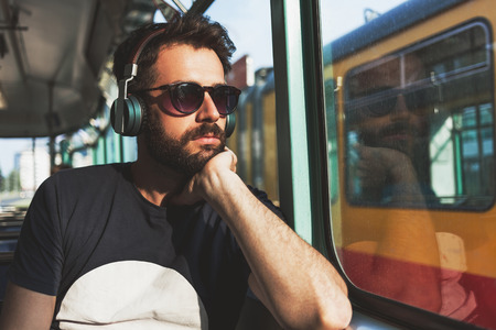 Young man riding in public transport listening to the music