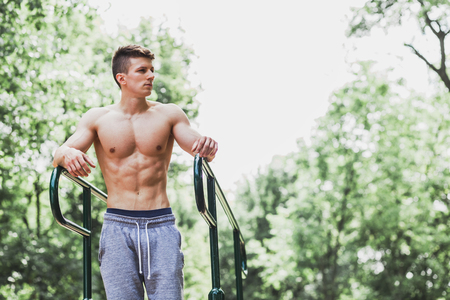Young muscular man standing by the bars in an outdoors gym