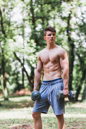 Young muscular man posing with weights outdoors