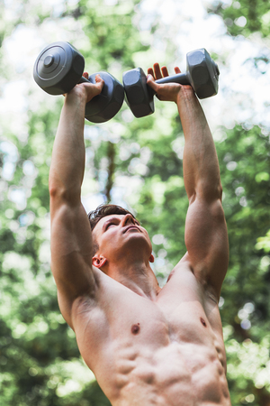 Muscular young man lifting weights outside in the park