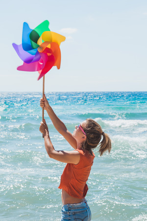 Young woman holding colorful windmill on the beach Archivio Fotografico
