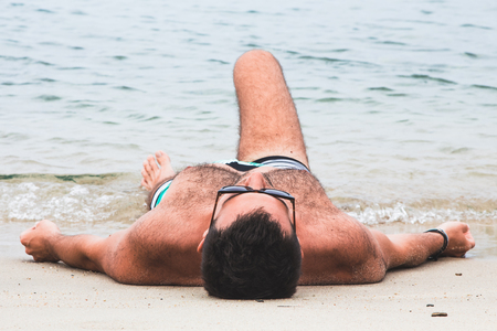 Young man lying on the beach by the water