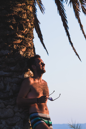 Young man enjoying sunset by the sea leaning on palm tree