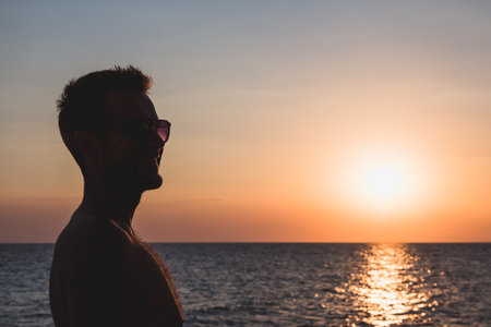Silhouette of a young man enjoying sunset by the sea Archivio Fotografico