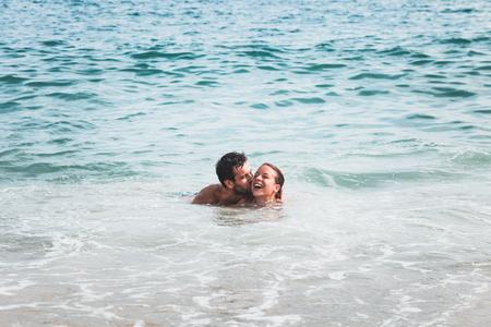 Giovane coppia in amore baciando nel mare