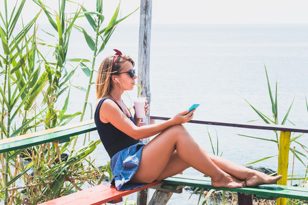 Young woman enjoying music and cold drink in a beach bar