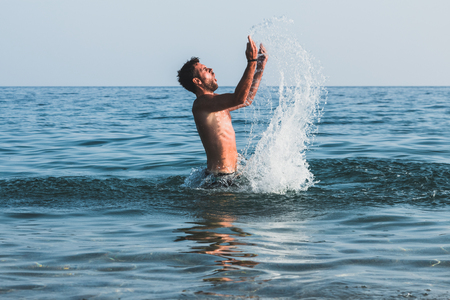 Young man splashing a water in the sea