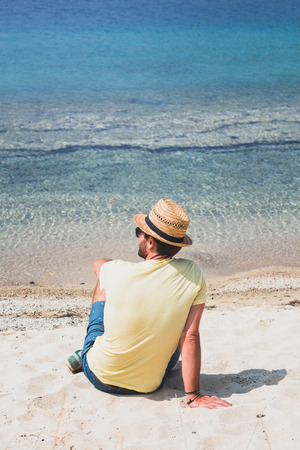 Giovane uomo seduto sulla spiaggia guardando il mare
