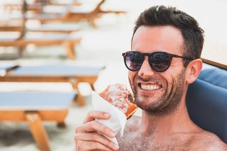 Young man eating chocolate doughnut on the beach