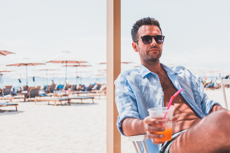 Young man drinking fresh orange juice in the beach bar Archivio Fotografico