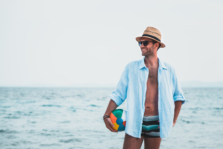Young man holding ball at the beach Archivio Fotografico