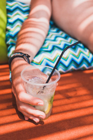 Close-up of a hand holding a glass of lemonade on the beach