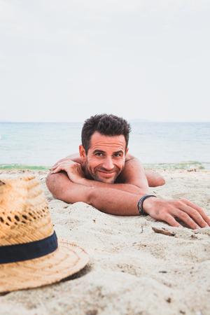 Giovane uomo sulla spiaggia che si trova nella sabbia