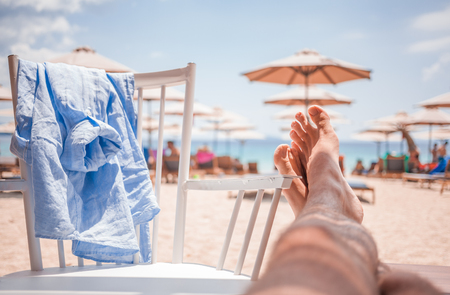 Mans legs stretch out in a lounge bar on the beach Archivio Fotografico