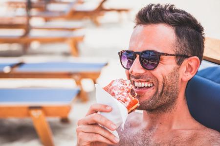 Giovane uomo bello mangiare ciambella sulla spiaggia