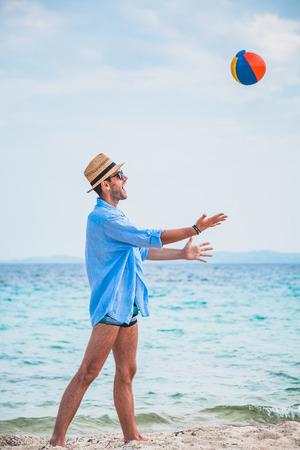 Giovane uomo bello che gioca sulla spiaggia con una palla