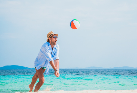 Young handsome man playing on the beach with a ball Archivio Fotografico