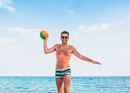 Giovane uomo bello sulla spiaggia che passa la palla nella macchina fotografica