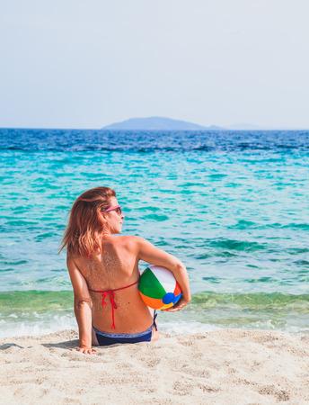 Giovane donna seduta in spiaggia e in possesso di una palla