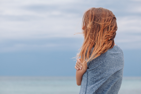 Woman alone and depressed at seaside Stock Photo