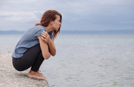 Woman alone and depressed on the bridge Stock Photo