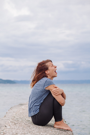 Woman alone and depressed screaming on the bridge Stock Photo