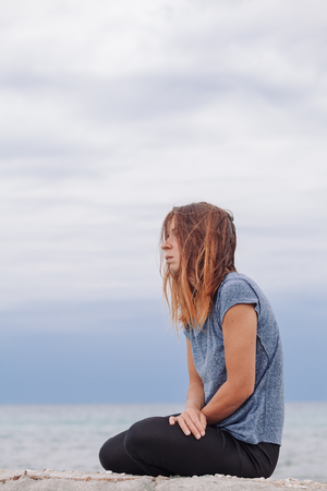 Vrouw alleen en depressief aan de kust