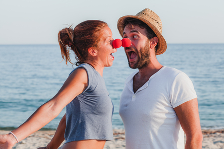 Funny young couple in love on the beach