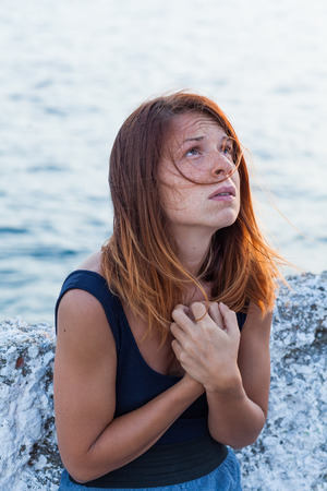 Young woman feeling sad by the sea Stock Photo