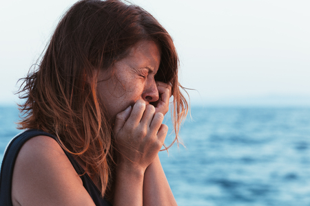 Young woman feeling sad by the sea 스톡 콘텐츠