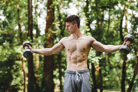 Young fit man lifting weight in the park 스톡 콘텐츠